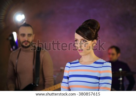 Portrait of beautiful singer with big eyes and dark hair in a striped dress in front of a drummer and guitar player - stock photo