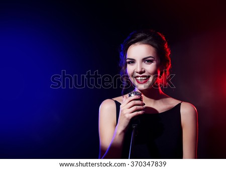 Portrait of beautiful singing woman on dark background - stock photo