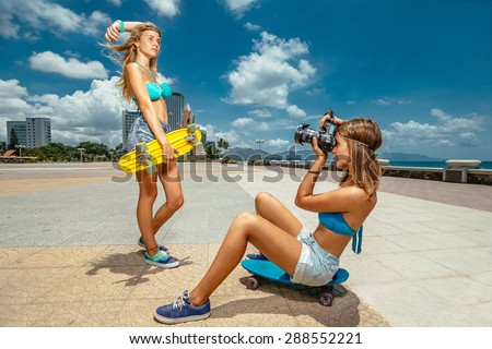 Portrait of beautiful skateboarding woman on skateboard and girl making photos at summer green park. - stock photo