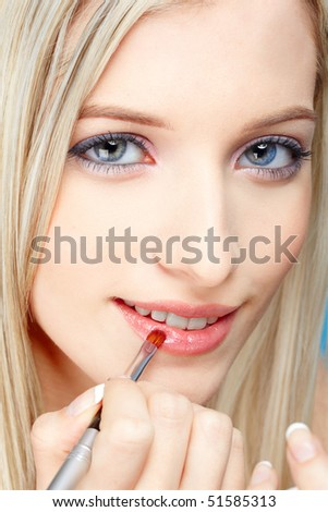 portrait of beautiful slavonic blonde girl making up on blue