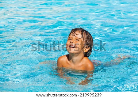 Portrait of beautiful small laughing boy in water - stock photo