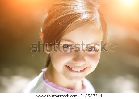 Portrait of beautiful small smiling girl with brunette hair and blue eyes in white blouse looking away standing sunny day outdoor on natural background closeup, horizontal picture - stock photo