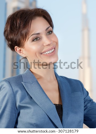 Portrait of beautiful smart business woman in the office on luxury buildings background, working in great successful company - stock photo