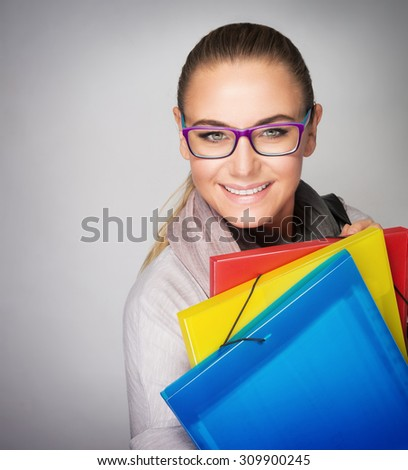 Portrait of beautiful smart student girl wearing glasses, standing with colorful folders over gray background, ready to receive new useful knowledge - stock photo