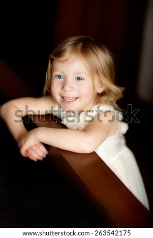 portrait of beautiful smiling blond girl in the cream dress - stock photo