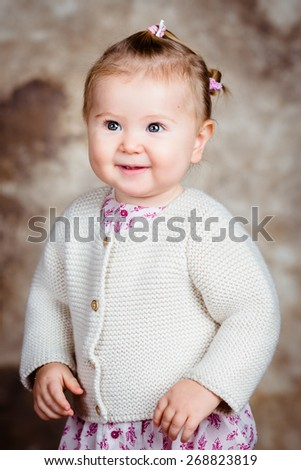 Portrait of beautiful smiling blond little girl with big grey eyes and plump cheeks. Studio portrait on brown grunge background - stock photo
