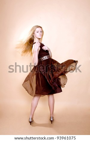 Portrait of beautiful smiling blonde teen girl with hair and brown dress flying. Isolated on beige background with clipping path - stock photo