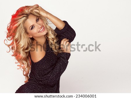 Portrait of beautiful smiling blonde woman with curly long hair. - stock photo