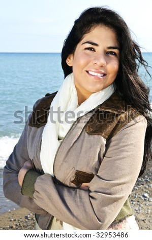 Portrait of beautiful smiling brunette girl at cool windy beach