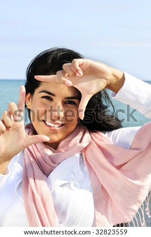Portrait of beautiful smiling brunette girl framing her face at beach