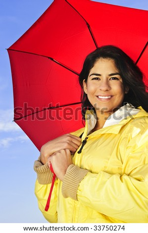 Portrait of beautiful smiling brunette girl wearing yellow raincoat holding red umbrella