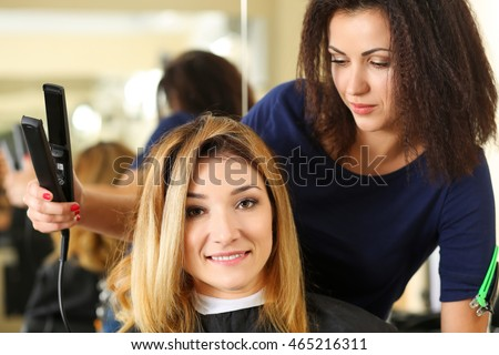 Portrait of beautiful smiling brunette hairdresser hold curling tongs and make wave to blonde customer. Keratin restoration, latest trend, fresh idea, hair straightener iron, evening makeup concept