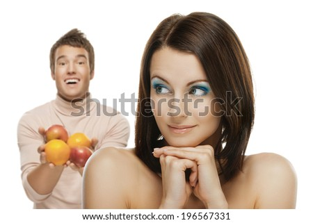 portrait of beautiful smiling brunette man giving apple to confused happy woman - stock photo