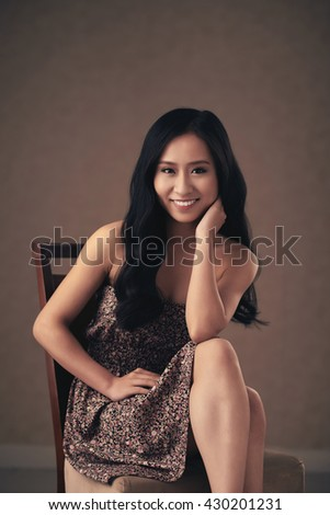 Portrait of beautiful smiling brunette sitting on chair