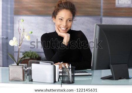 Portrait of beautiful smiling businesswoman sitting at desk.