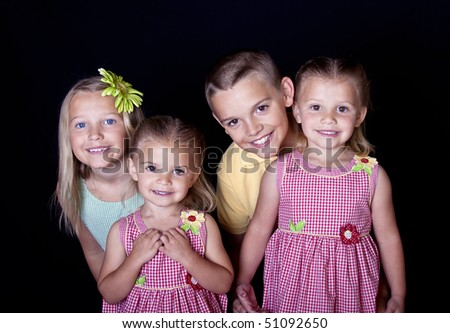 Portrait of beautiful, smiling children on a black background. - stock photo
