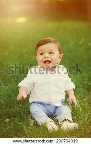 Portrait of beautiful smiling cute baby boy. 8 month old little child playing outside in green summer or spring park. Boy sitting alone on green grass at sunset time. - stock photo