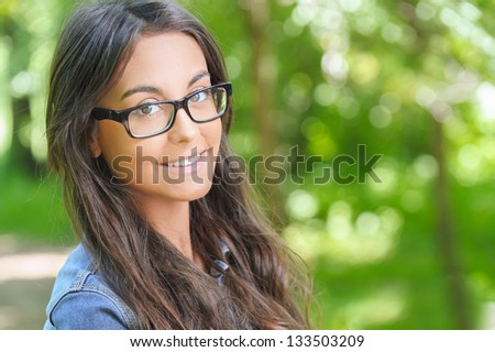 Portrait of beautiful smiling dark-haired young woman, against summer green park. - stock photo