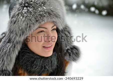 portrait of beautiful smiling female in luxurious fur head cloth outdoor in winter - stock photo