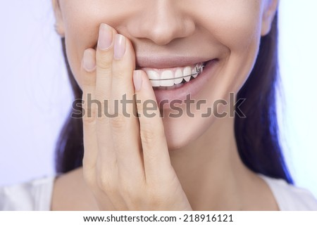 Portrait of Beautiful smiling girl covering with hand her retainer for teeth - stock photo