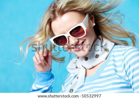 Portrait of beautiful smiling girl wearing sunglasses posing at camera - stock photo