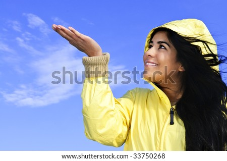 Portrait of beautiful smiling girl wearing yellow raincoat looking up checking for rain
