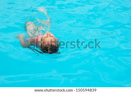 Portrait of beautiful smiling little girl at resort in warm comfortable pool. - stock photo