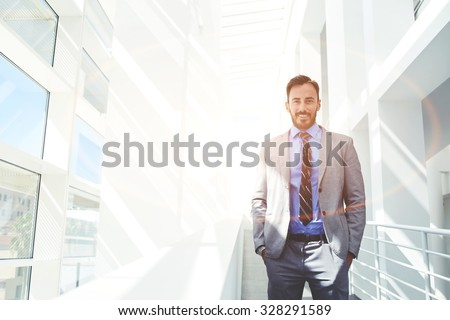 Portrait of beautiful smiling man prosperous economist dressed in corporate clothes posing while standing in modern office building, young happy intelligent lawyer posing with copy space area for text - stock photo