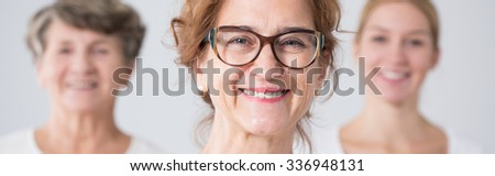 Portrait of beautiful smiling mother in glasses - stock photo