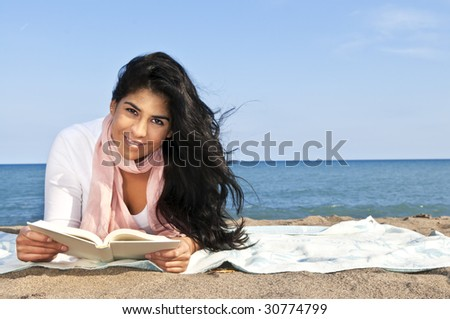 Portrait of beautiful smiling native american girl reading book at beach