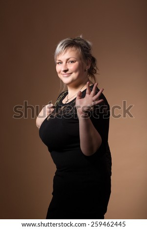 portrait of beautiful smiling plus size young blond woman posing with designer handbags and black dress - stock photo