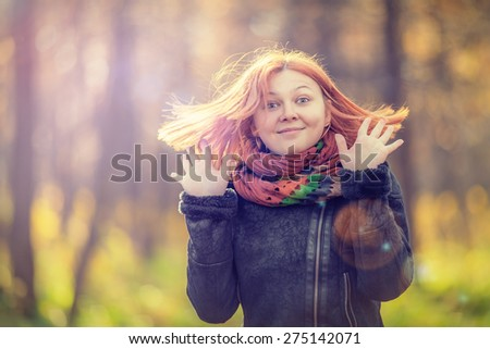 Portrait of beautiful smiling red-haired woman in autumn park (shallow dof) - stock photo