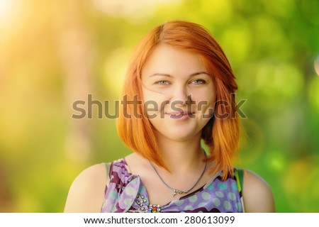 Portrait of beautiful smiling red-haired woman (shallow dof) - stock photo