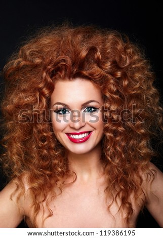 Portrait of beautiful smiling redhead woman girl with bright makeup with red lips with perfect skin isolated on black