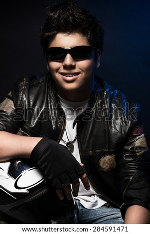 Portrait of beautiful smiling teen boy biker over dark blue background, wearing stylish biker's outfit and holding helmet, stylish fashion look