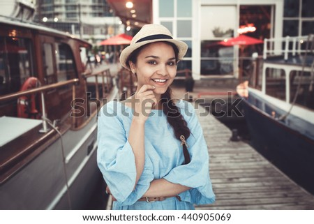 Portrait of beautiful smiling white Caucasian brunette girl on boat yacht pier quay, in blue dress and straw hat, navy maritime retro vintage style concept - stock photo