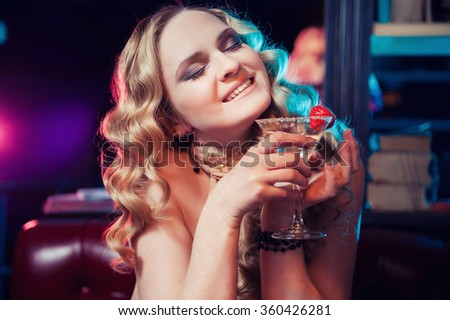 Portrait of beautiful smiling woman having a martini at the bar - stock photo