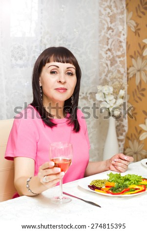 Portrait of beautiful smiling woman in dinner with glass of wine - stock photo