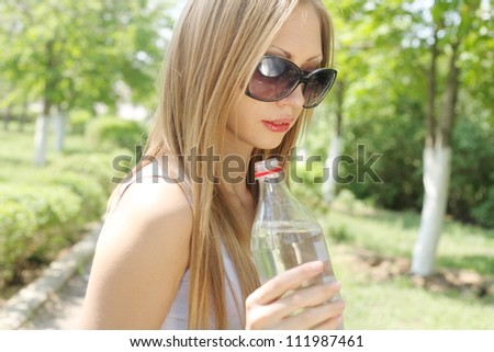 Portrait of beautiful smiling woman in sunglasses with bottle of water in hands, closeup shot, outdoors, summer - stock photo