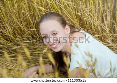 Portrait of beautiful smiling woman in the wheat field - stock photo