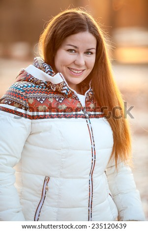 Portrait of beautiful smiling woman in white down jacket in the sunlight - stock photo