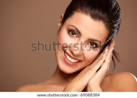 Portrait of beautiful smiling woman isolated on beige