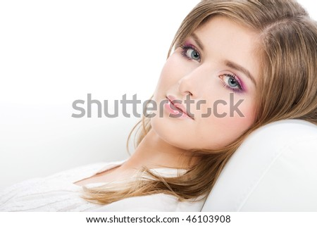 Portrait of beautiful smiling woman laying on white sofa