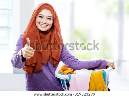 portrait of beautiful smiling woman wearing hijab carrying laundry basket and giving thumbs up - stock photo