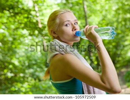 Portrait of beautiful smiling woman with bottle of water after jogging