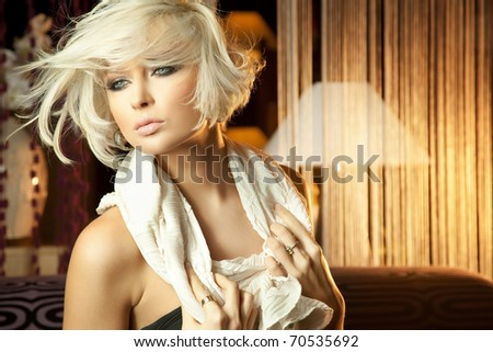 Portrait of beautiful smiling young blond woman relaxing at home - stock photo