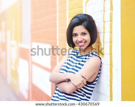 Portrait of beautiful smiling young hipster latin hispanic girl woman with short hair bob, in blue white striped tshirt, leaning on brick wall in city looking in camera, lifestyle fashion concept - stock photo