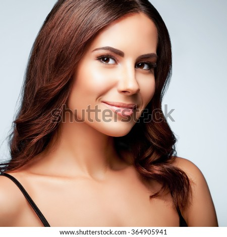 portrait of beautiful smiling young woman in black tank top clothing, on bright grey background