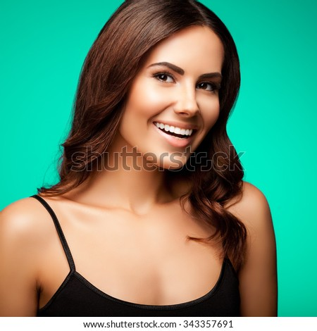 portrait of beautiful smiling young woman in black tank top clothing, on green background