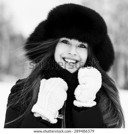 Portrait of beautiful smiling young woman in luxurious fur head cloth outdoor in winter in black-and-white - stock photo